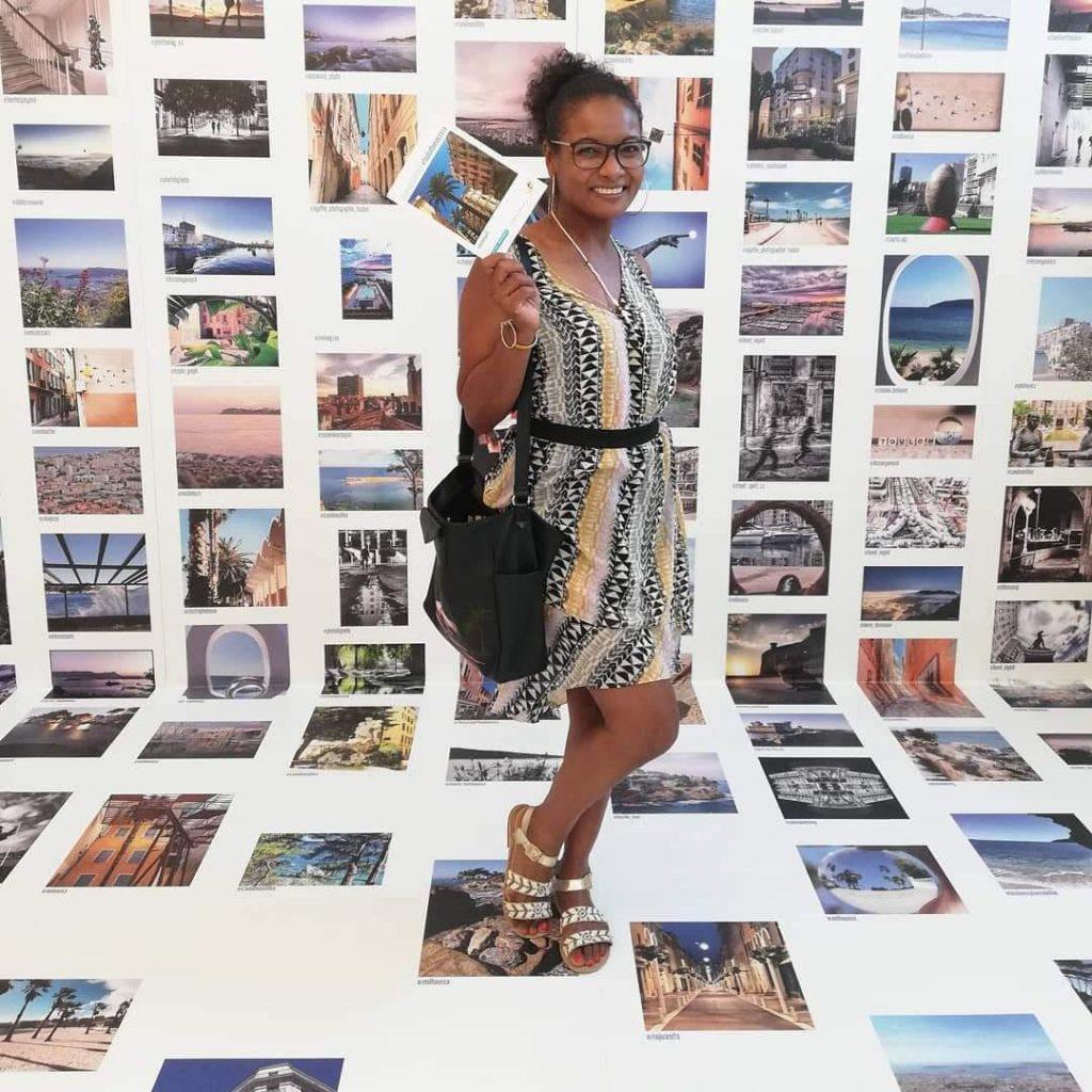 Toulon by Julia : jeune femme posant devant plein de photographies de lieux culturels.